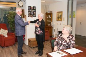 voorzitter André van Rijswoud overhandigt de sleutel van de herinneringskoffer aan Karin van Wanrooij (zorgbegeleidster de Venloene).