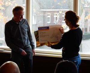 Penningmeester Ad Vermeer neemt de cheque in ontvangst.
